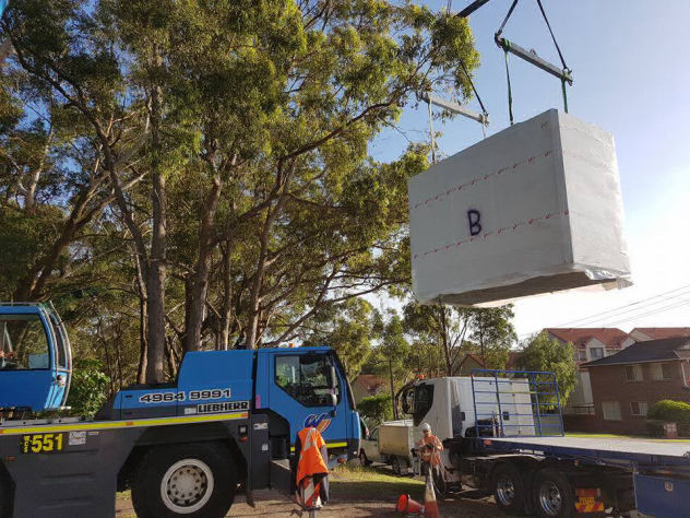 Mobile crane delivers a stack of MAAP hybrid modular panels to the building site